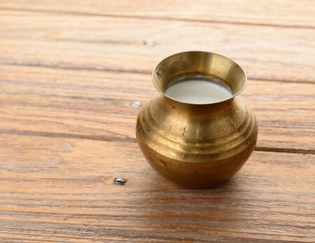 tarnished: a brass pot of milk on wood texture