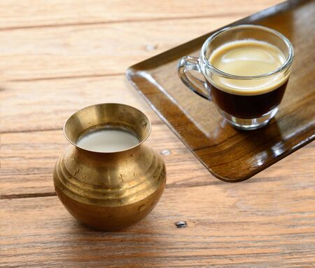 tarnished: Cup of espresso coffee and a brass pot of milk on wood texture Stock Photo