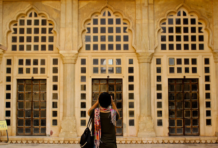 eloquent: Photograpahy: An enthusiast taking picture of the symmetry of doors that is in front of her. Stock Photo
