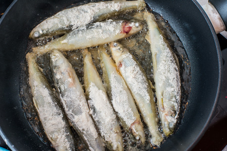 fish dinner: Fried small tasty fish on a barbecue grill  hotplate