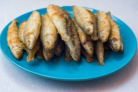 textille: Fried fish lays on a white plate over gray tablecloth Stock Photo