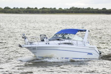 motor: motor boat floats on the river in cloudy weather Stock Photo