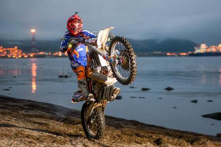 Yuzhno-Sakhalinsk , Russia - motorcycle Enduro riding wheelies on the beach Redactioneel