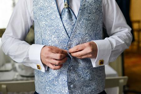 cufflinks: Close-up of a man in a tux fixing his cufflink. groom bow tie cufflinks