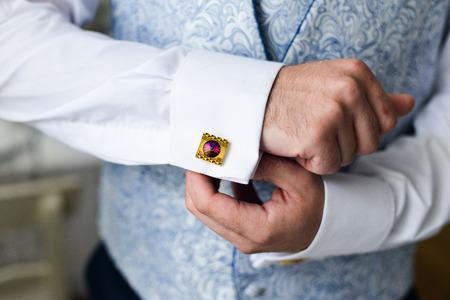 cufflink: Close-up of a man in a tux fixing his cufflink. groom bow tie cufflinks