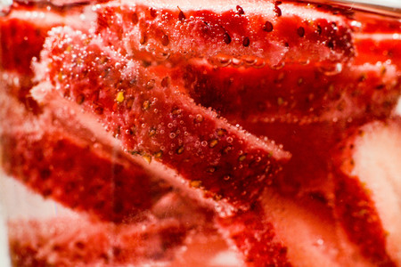 Strawberry berry in water in vials of gas. Light background, close up
