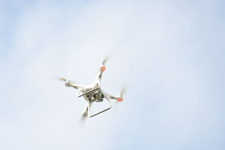 hovering: white drone hovering in a bright blue sky Stock Photo