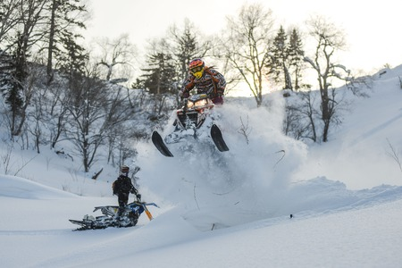 rider moving snowmobile in winter forest in the mountains of Sakhalin Island