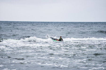 Kayak surfer over the crest of a wave in rough sea