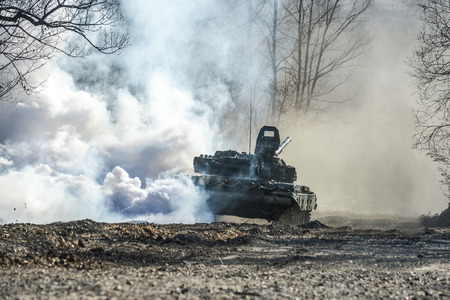 Russian tank t-72 shot on a forest road smokescreen Stock Photo