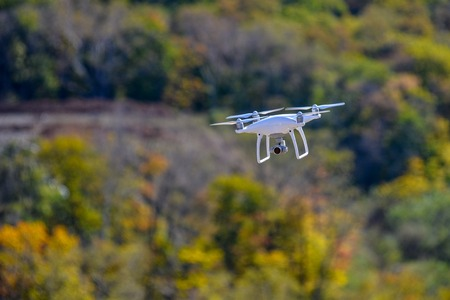 paddler: Drone quadcopter with high resolution digital camera flying at the backyard of a forest