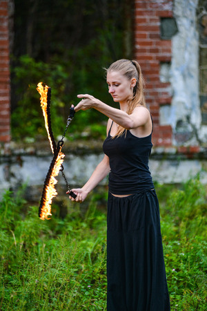 Girl in a black suit with flaming torches. fire Stock Photo