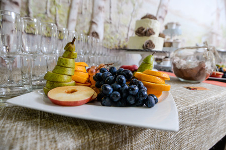 Fresh fruit salad made of grape, strawberry, plum and nectarine served on plate with lemon above, photographed overhead on dark wood with natural light