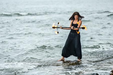 coordinacion: jugar con la demostración del fuego en la orilla del mar Foto de archivo
