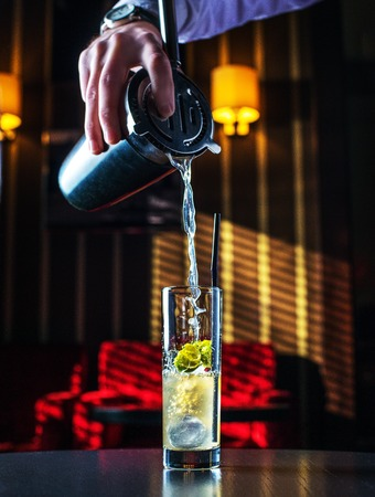 Barman at work, preparing cocktails. pouring Mai tai to cocktail glass.