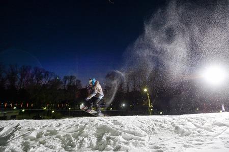 Snowboarder jumping at night Reklamní fotografie