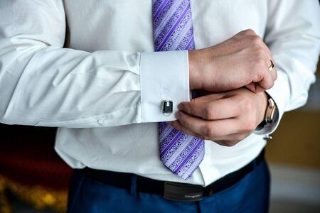 cufflink: man in a tux fixing his cufflink