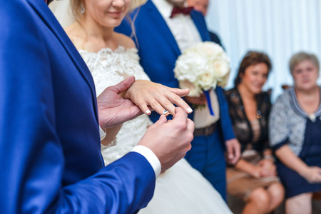 fingers put together: marriage hands with rings. birde wears the ring on the finger of the groom