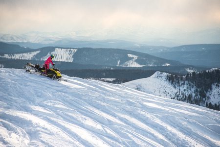 Rider on the snowmobile in the mountains 版權商用圖片