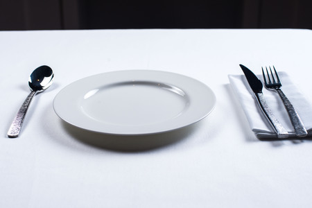 white plate with a knife and fork on a white background