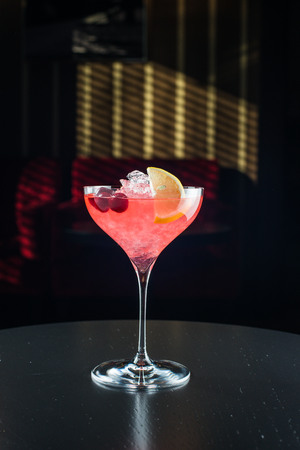 Barman at work, preparing cocktails. pouring cosmopolitan to cocktail glass. Stock Photo