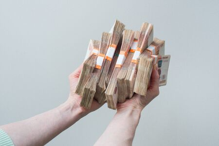 path to wealth: hand holding many of the Russian banknotes