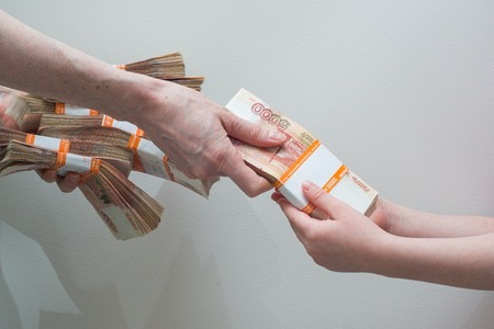 childrens and womans hand with stack of Russian money