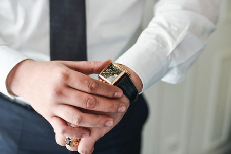 cuff link: businessman clock clothes, businessman checking time on his wristwatch.