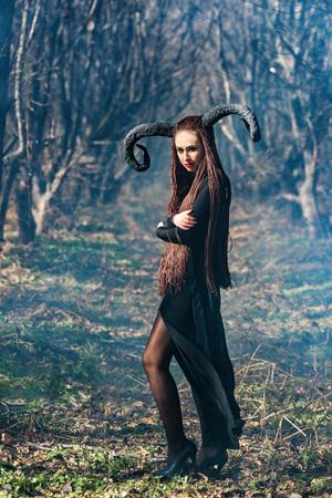 ハロウィーンの妖精魔女レインコートと角として服を着た美しい女性 写真素材