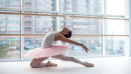 Young and incredibly beautiful ballerina is posing and dancing in a white studio full of light.