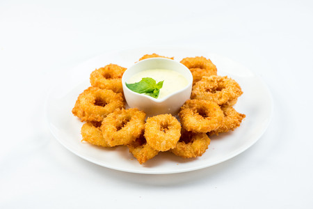 Squid rings fried in batter with white sauce on white plate on white background