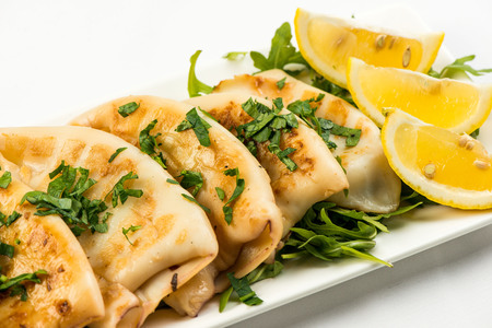 body of squid fried with lemon on white plate on white background
