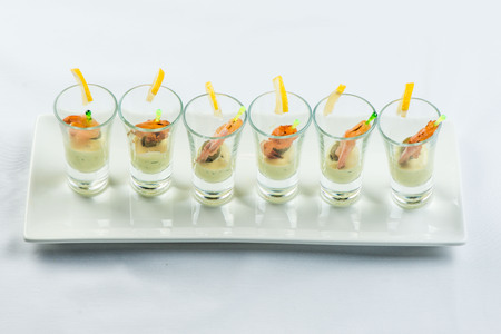 individual Cocktail Shrimp shot glasses with delicious homemade tartar spicy sauce decorated with parsley leaf for Christmas dinner or cocktail party, bokeh background, close-up