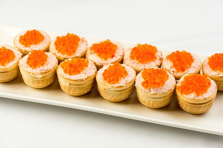 Tartlets with cheese and red caviar. Selective focus. Copy space
