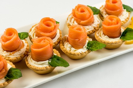 The salted smoked salmon in the basket is made in the form of a rose on a white plate Standard-Bild