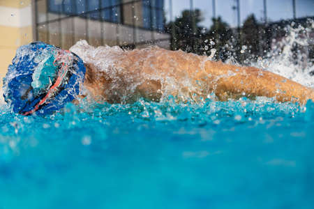 Man swims using breaststroke technique . pool turquoise water
