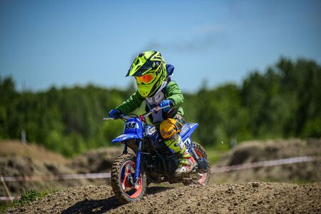 KHABAROVSK, RUSSIA - june 16, 2019 :Racer child on motorcycle participates in motocross cross-country in flight, jumps and takes off on springboard against sky. Concept active extreme rest teenager. Redakční