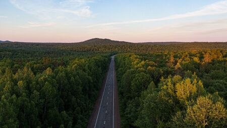 Top view of the dirt road and green spring forests in bright sunset colors. Beautiful landscape from the air, photograph from the drone