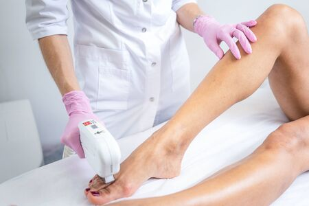 Laser hair removal on womens legs . white background close up Stok Fotoğraf