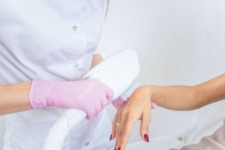 laser hair removal. Closeup of beautician hair removal hands of a young woman. Procedure Of Cosmetic Hair Removal In Cosmetic Beauty Clinic. Hairless Smooth And Soft Skin. body care. high resolution