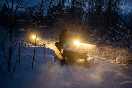 snowmobile in the evening goes through the winter forest. headlights. night road through the winter forest. snowmobile at night.