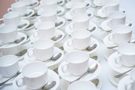 A lot of white coffee cups. Top view on many stacked in rows of empty clean white cups for tea or coffee
