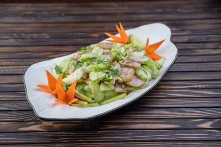 Typical Chinese salad of cucumbers and pork in a white plate on a wooden background Stockfoto - 140237154