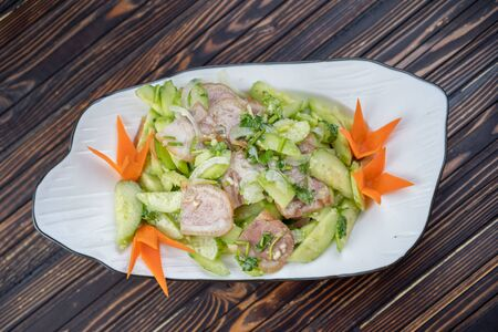 Typical Chinese salad of cucumbers and pork in a white plate on a wooden background .
