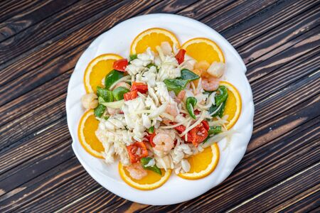 Shrimp in Warm Seafood Salad in a white plate.