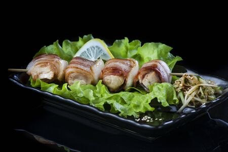 meat on wooden skewers, pork, chicken, fish, scallop, beef, shrimp in a black plate on a black background. Stockfoto