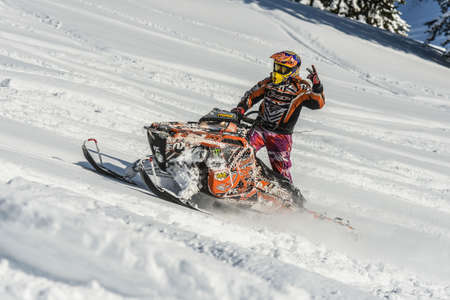 Athlete on a snowmobile moving in the mountains