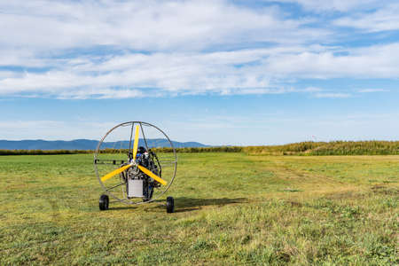 Moto-paraglider on green grass with blue sky. Stockfoto