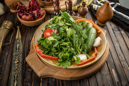 Bright fresh green salad leaves with red tomatoes, cucmbers and radish in the white bowl on wooden background Stockfoto