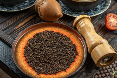 Heap of hot black pepper in bowl on a wooden table